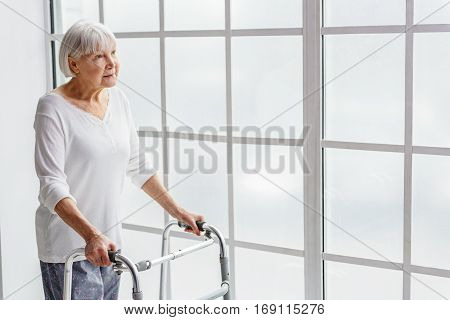 Outgoing female pensioner keeping gutter frame while looking at window