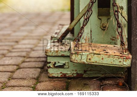 Vintage antique objects concept. Old fashioned rotten green wooden weighing machine in sunlight