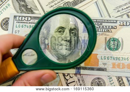 100 Us Dollars Under A Magnifying Glass. Close-up