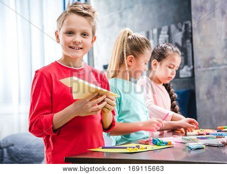 Kid playing with paper plane schoolchildren molding colorful plasticine