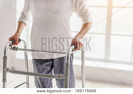 Focus on pensioner holding gutter frame in her hand while standing near closed window