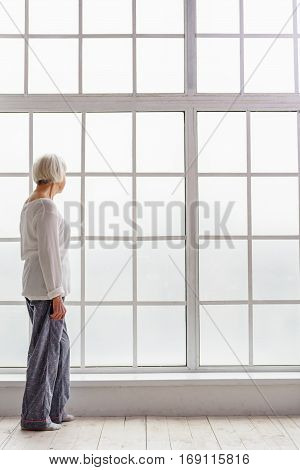 Thoughtful grandmother watching at wide big closed window while standing near it in clinic poster