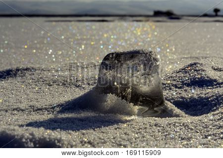 Siberia, Lake Baikal. Icicle in the snow in the sun. Snow around the sparkling color of the raibow. Like scattered gems. Halo effect on snow.