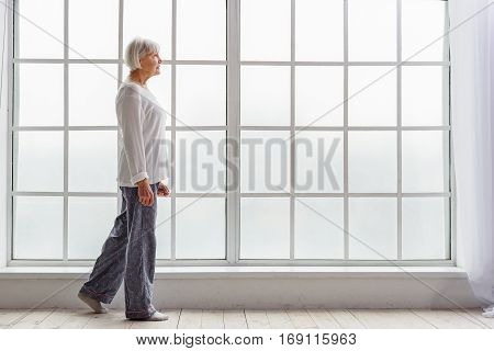 Smiling pensioner in pajama going in hospital apartment near window