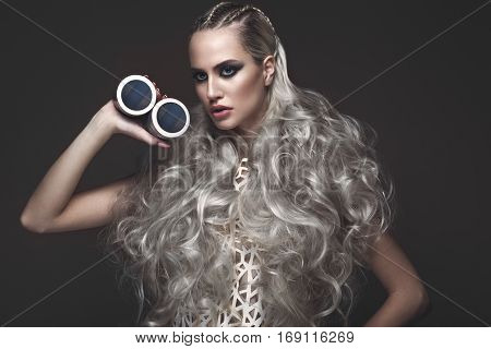 Beautiful girl in art dress and avant-garde hairstyles with cosmetic products in her hands. Beauty face. Photos shot in the studio.
