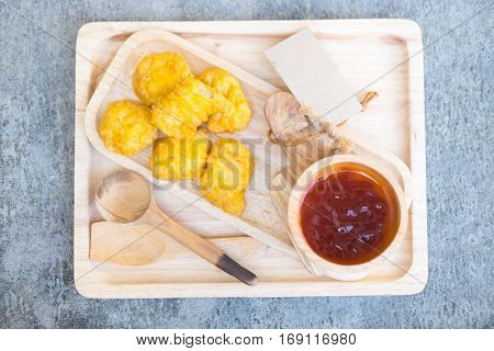 Tasty homemade chicken nuggets with ketchup on wood plate