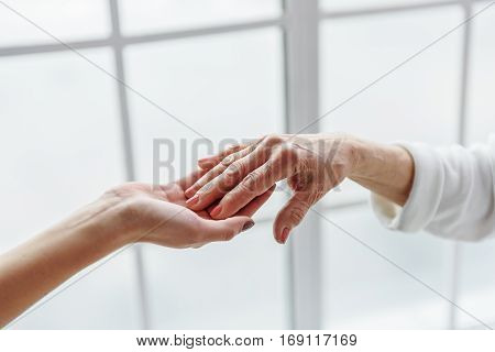 Your health in safe hands. Focus on close up two holding hands of young female doctor and old woman
