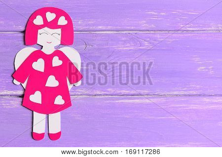 Angel doll with hearts made of cardboard. Cute angel on lilac wooden background with copy space for text. Valentine's day background. Top view