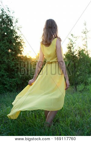 The girl in a yellow long dress stands back and looks at the setting sun. State of mind. Recreation. Solar flare.