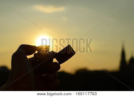 Silhouette of man's hands that keeps iron lighter at sunset. Smoking. Harm.