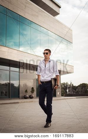 A successful man is a businessman in the background of a glass building in the strict style clothing holding office folder in hand. White shirt dark pants sunglasses. Toning