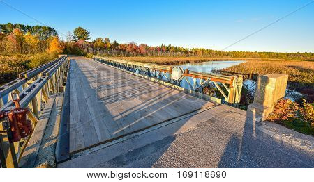 Wide angle view of clear blue sky, late afternoon sunshine, casts long shadows on a light steel and timber bridge, single point perspective over a lake in Ontario, Canada.