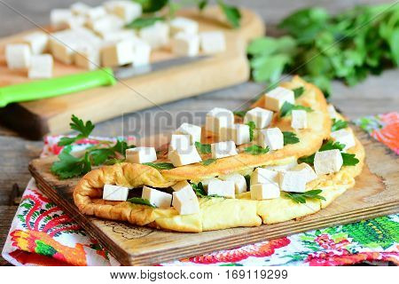 Stuffed omelette on a wooden board and a textile napkin. Omelette stuffed with tofu and garnished with parsley. Cut tofu on a cutting board, knife, parsley sprigs on a wooden table. Closeup
