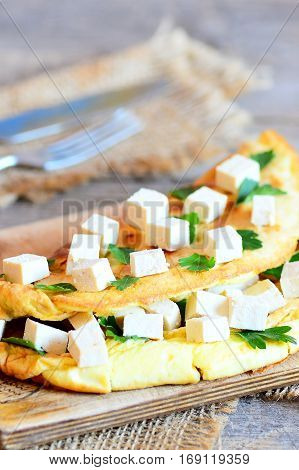 Tofu parsley omelette recipe. Home golden omelette with tofu and fresh parsley on a wooden table. Rustic style. Closeup. Vertical photo