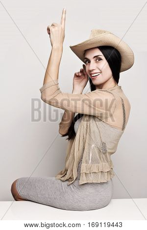 Attractive young cowgirl posing in cowboy hat