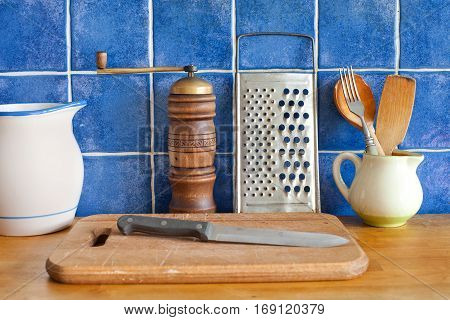 Kitchen interior still life. Vintage utensils ceramic pitchers, cutting board, knife, wooden spoon, pepper and metallic grater. Blue tiled wall background photo