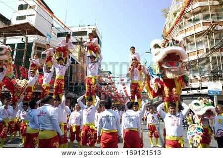NAKHONSAWAN ,THAILAND - JANUARY 31,2017 : Unidentified people dancing with Chinese Lion of Gods doing ritual at worship altar table during the Chinese New Year celebrations in Nakhonsawan Province , Middle of Thailand.