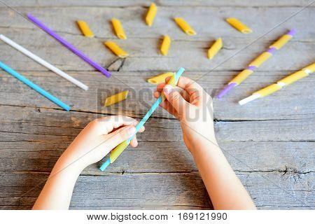 Game idea for children to help develop fine motor skills. Small child holding a straw and a dried pasta in his hands. Materials for stringing pasta. Wooden background