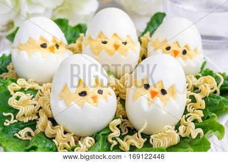 Little chicken in nest deviled eggs served with salad and dry ramen on white plate horizontal