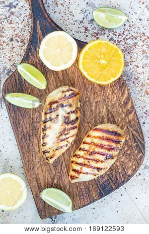 Grilled chicken breast in citrus marinade on salad leaves and wooden cutting board vertical top view