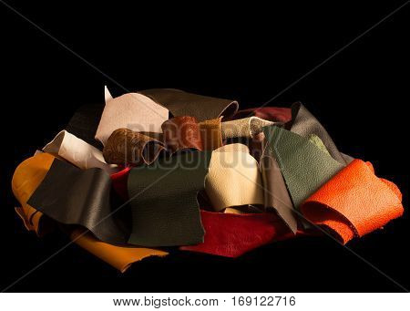 Bundle of different colors and textured leather scraps, piled together. Isolated on a black background.