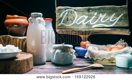 Lighted wood sign above counter in dairy shop. Milk, butter milk, cream, yogurt, farmer cheese, eggs on counter. Concept for dairy store. Soft focus