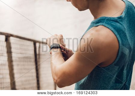 Close up shot of young man outdoors using a smartwatch to monitor his progress. Male runner resting and checking his performance on smart watch device.