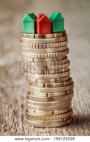 Real estate mortgage concept with small houses on top of stacked coins