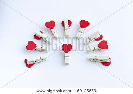 wooden clothes pin or cloth pegs with heart shape design on a white background