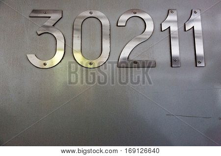 Steel numbers in metallic bolts are screwed to the wall