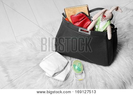 Mothers bag with accessories on fluffy carpet