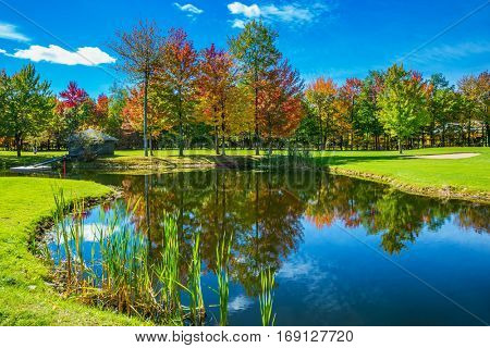Park of fantastic beauty. Golf Club on the road to Bromont, French Canada. Red, orange and green autumn foliage is reflected to clear water of the lake. Concept of Golf tourism