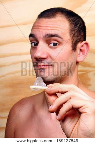Young Handsome Boy Shows And Keeps A Condom