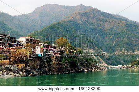 View to Ganga river, colored houses and lakshman jhula bridge, Rishikesh, India