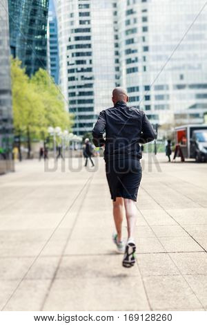 African man jogging in urban setting, La Defense, Paris