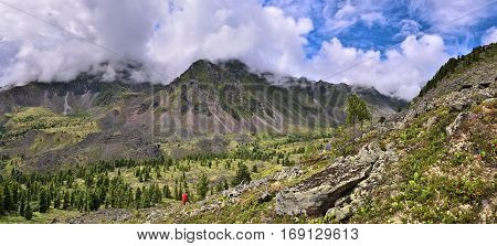 Panoramic view of mountain valley from slope. Siberian woodlands and alpine tundra. Eastern Sayan. Siberia. Russia