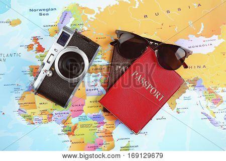 Adventure concept. Camera, sunglasses, passports on map