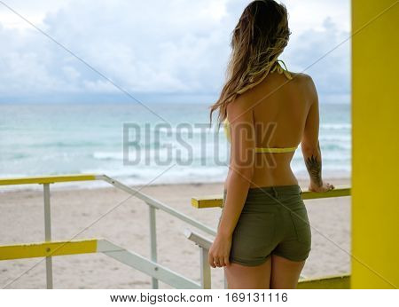 Beautiful woman in bikini at lifeguard station, Miami,