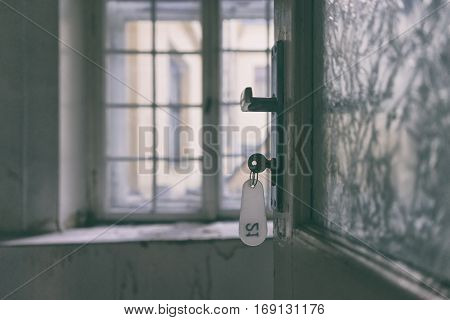 The key to a room on the old plastic FOB to lock the glass doors into an empty room with bars on the window in the yard
