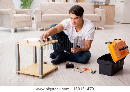 Man assembling shelf at home
