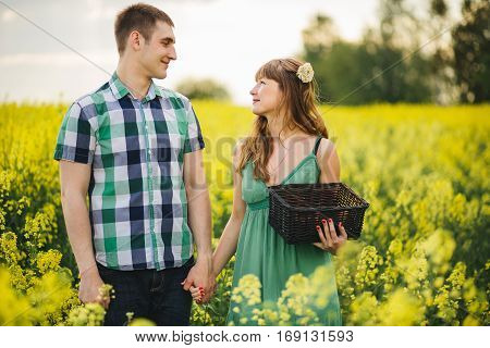 Happy couple holding bu hands and looking each other face to face and smiling. Handsome boyfriend wearing checked shirt and pretty girlfriend wearing green dress with flower in hair. Summertime.