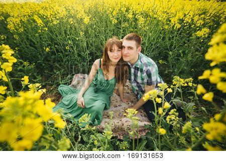 Couple sitting among yellow flowers in meadow embracing touching by face each other. Girlfriend wearing green dress husband in checked shirt. Picnic outdoor in summertime.
