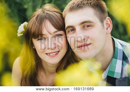 Portrait of couple of young boyfriend and girlfriend smiling at camera. Couple among flowers touching by face each other. Brunette with flower in long hair wearing dress man in checked shirt.