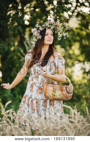 Attractive brunette girl with long hair wearing dress in floral print with wrath of wildflowers on head posing outdoor. Woman walking in meadow and holding basket in hand. Summer season.