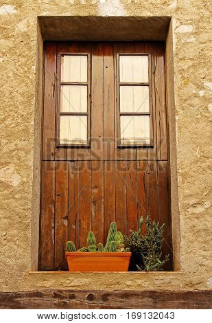 Wooden window with pots of cactus in a spanish village Besalu