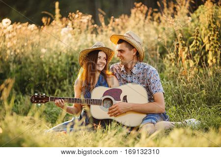 Romantic place in field when happy couple sitting on grass smiling and singing. Wife and husband looking each other and playing on guitar. Girl and boy wearing hats having fun together outdoors.