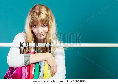 Smiling pretty woman grabbing clothing in wardrobe. Young undecided shopper girl takes all from mall shop. Shopaholic concept.