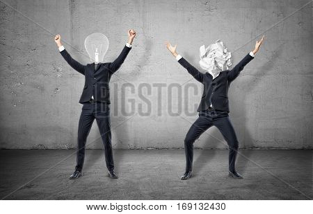 Two businessmen on concrete background, one has a lamp in pace of his head, and another has a white ball of paper. Business communication. Corporate world. Fitting in.