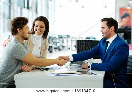 Salesman and customer shaking hands congratulating each other at the dealership showroom. poster