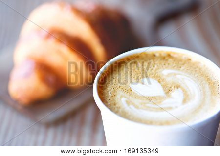 close-up of beautiful heart shaped latte art with croissant pastry in the background in cafe